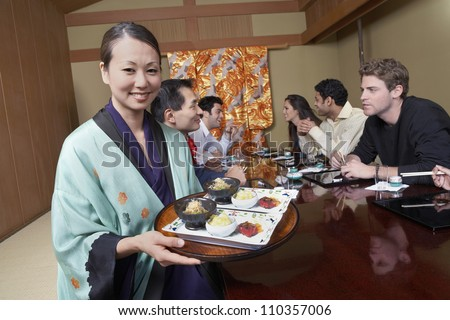 Waiter holding plates to serve food to people at restaurant - stock photo