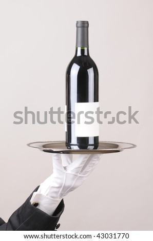 Waiter holding red wine bottle on tray over gray background vertical format hand and arm only - stock photo