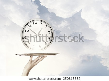 Waiter holding silver platter with white alarm clock