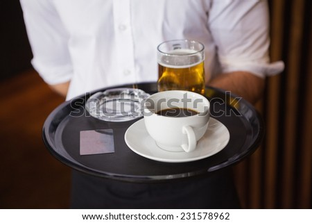 Waiter holding tray with coffee cup and pint of beer in a bar - stock photo