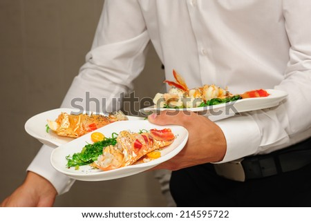 Waiter holds plates with lobsters - stock photo