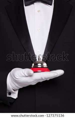 Waiter in black tie and white gloves holding a service bell.
