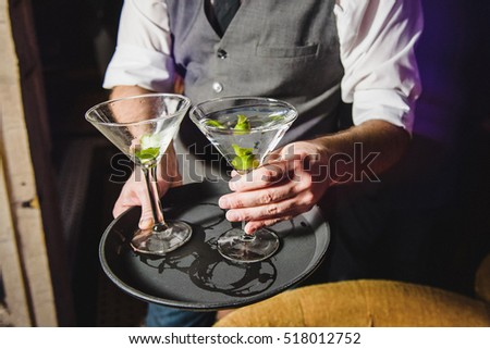 Waiter in grey waistcoat puts cocktail on the tray