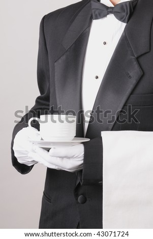 Waiter in Tuxedo holding a coffee cup with a towel draped over his arm torso only vertical format over gray background. Man is unrecognizable.