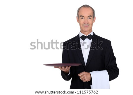 waiter in tuxedo holding a plate - stock photo