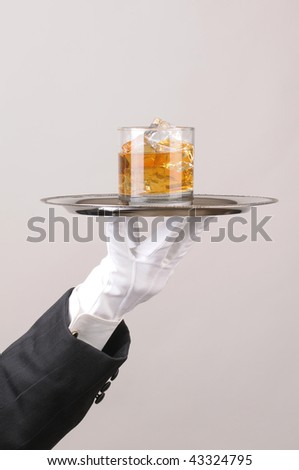 Waiter in tuxedo Presenting Cocktail on silver tray closeup vertical format hand and arm only - stock photo