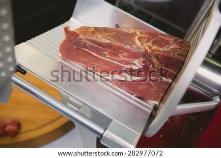 Waiter is slicing prosciutto in restaurant, toned image - stock photo