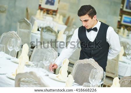 waiter man serving banquet table at restaurant - stock photo
