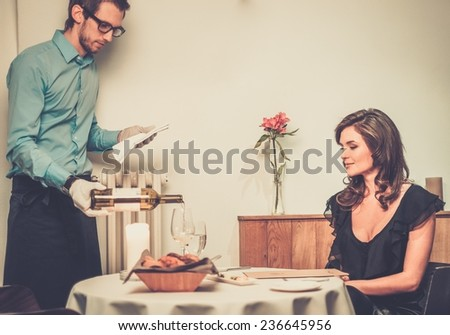Waiter offering wine to lady in restaurant  - stock photo