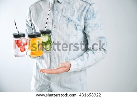Waiter offers three cold refreshment beverages from strawberry,orange,lime,mint,cucumber,ice and sparkling water in rustic jars to drink for sale on camera
