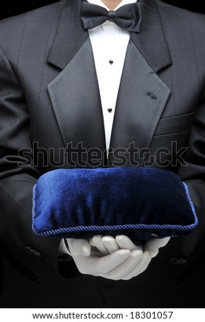 Waiter or butler holding a velvet pillow in front of his torso. Person is unrecognizable.