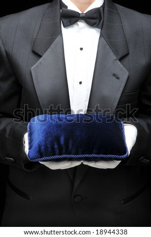 Waiter or Butler in Tuxedo with Blue Velvet Pillow held in His Hands in front of his torso. Person is unrecognizable.