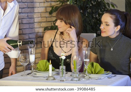 waiter pouring champagne into glass in a restaurant - stock photo