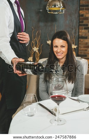 Waiter pouring red wine to a beautiful smiling woman - stock photo