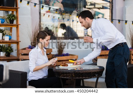 Waiter server at table working reading menu specials list for group of people