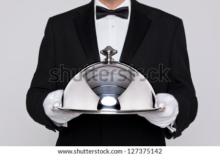 Waiter serving a meal under a silver cloche or dome - stock photo