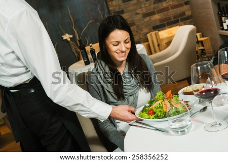 Waiter serving a plate of salad to a woman guest in a restaurant