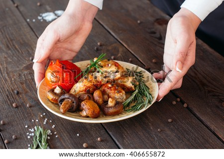 Waiter serving a shish kebab with tomato and mushrooms on wooden background. Chief decorating food for presentation in small cafe. Waiter serving shish kebab with fresh vegetables for retail.  - stock photo