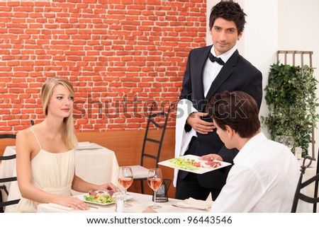 Waiter serving a young couple - stock photo