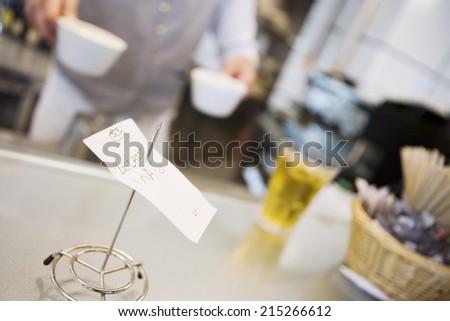 Waiter serving beverages in cafe, focus on check stub holder in foreground, close-up (tilt) - stock photo