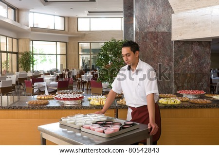 Waiter serving cake at restaurant. - stock photo