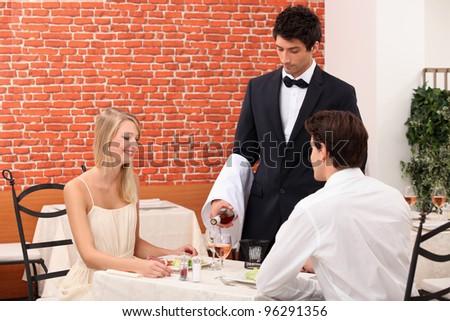 waiter serving couple - stock photo