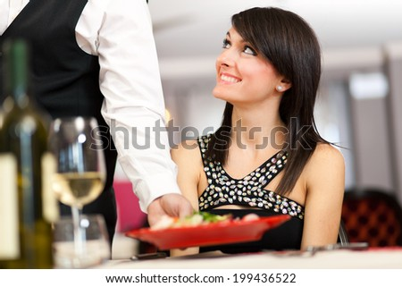 Waiter serving food in a luxury restaurant - stock photo
