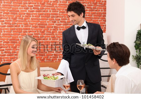 Waiter serving plate of food - stock photo