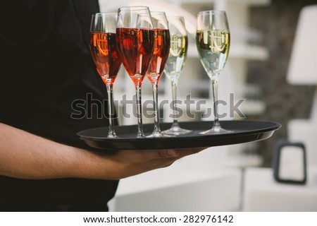Waiter serving red and white champagne on a tray - stock photo