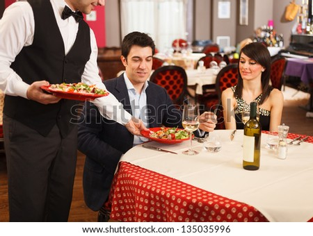 Waiter serving sea food to a couple - stock photo