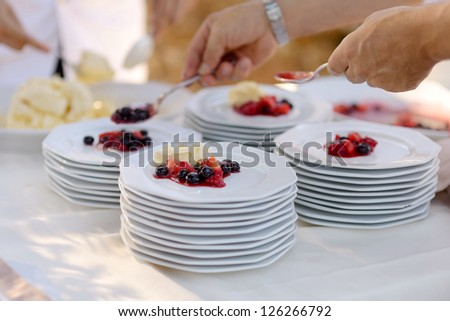 Waiter serving some plates with dessert - stock photo
