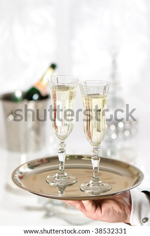 Waiter serving two glasses of champagne to dining table decorated for Christmas
