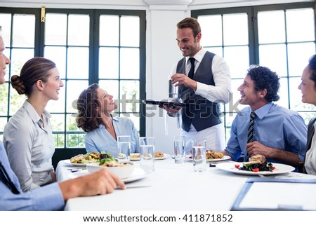 Waiter serving water to the business people in restaurant