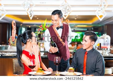 Waiter serving wine in restaurant - stock photo