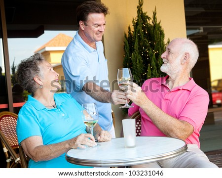 Waiter serving wine to a senior couple at a restaurant. - stock photo
