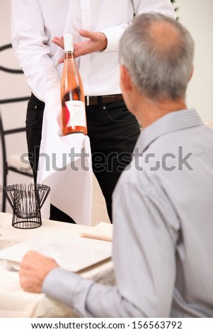 Waiter showing bottle of wine to man dining alone - stock photo