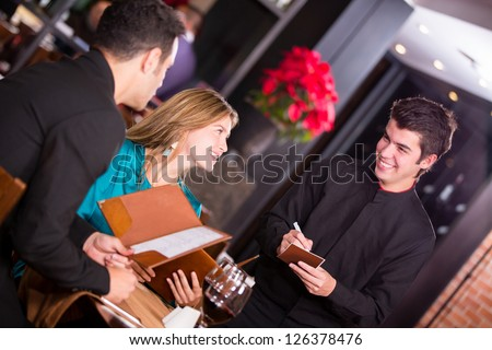Waiter taking an order from a couple at the restaurant - stock photo