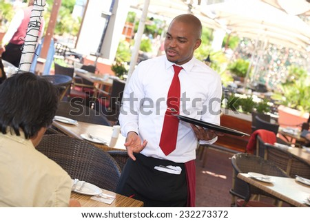 Waiter taking an order from customer in restaurant