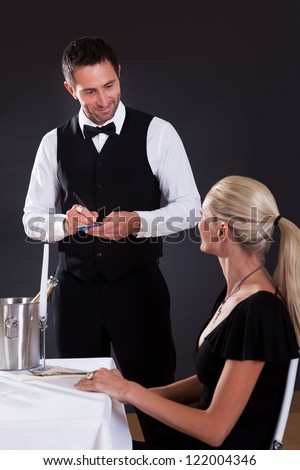 Waiter taking order from woman in restaurant - stock photo