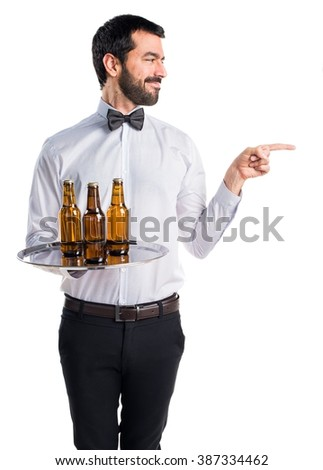 Waiter with beer bottles on the tray pointing to the lateral