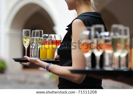 Waiter with dish of champagne, wine and juice glasses - stock photo