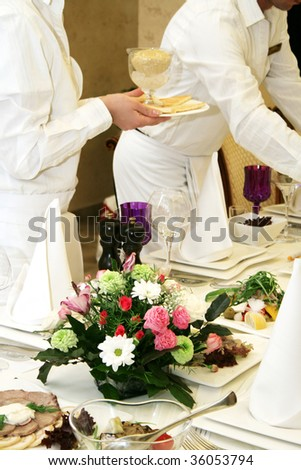 Waiters cover and serve a banquet table - stock photo