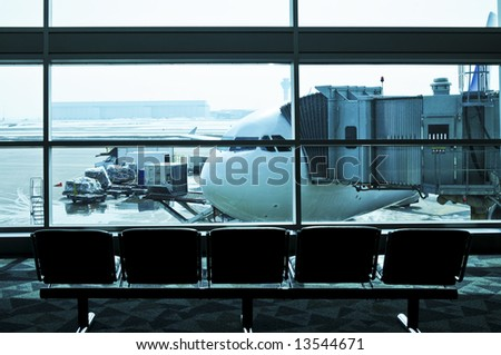 Waiting area of airport gate with airplane outside - stock photo