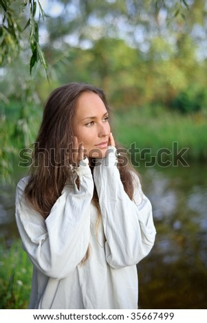 Waiting beautiful young woman on the river coast - stock photo