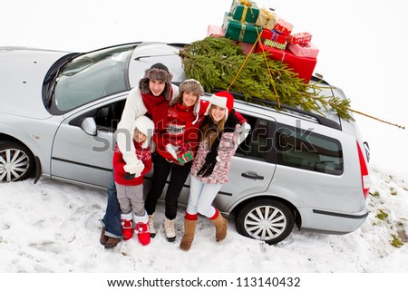 Waiting for Christmas  - the family is carrying  Christmas tree and gifts on the roof of the car - stock photo