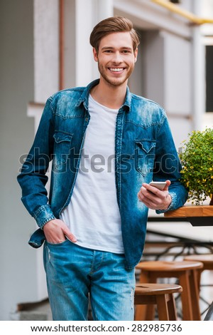 Waiting for his friends. Happy young man holding mobile phone and smiling at camera while standing at sidewalk cafe - stock photo