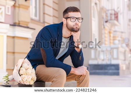 Waiting for his girlfriend. Thoughtful young man in smart jacket holding hand on chin while sitting on the bench with a bouquet of flowers laying near him  - stock photo