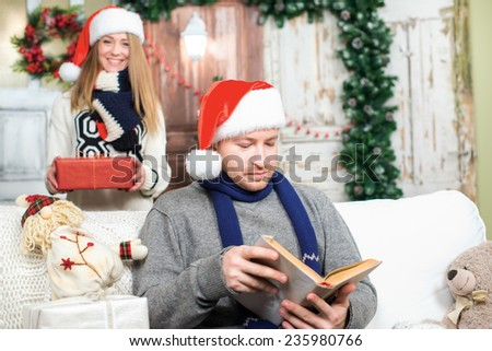Waiting for ideal Christmas present.. Young and beautiful couple is in festive New Year living room just before the Christmas. Girl is preparing to give New Year present to her boyfriend. - stock photo