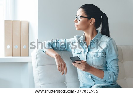 Waiting for important message. Beautiful young woman in glasses holding smart phone and looking at the window while sitting on the couch in office - stock photo