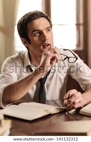 Waiting for inspiration to strike. Handsome young author sitting at the table with a pen in his hand and waiting for inspiration - stock photo